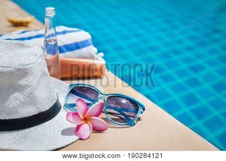 Sunscreen cream, straw hat, plumeria flower, towel and sunglasses near swimming pool - holiday tropical exotic concept