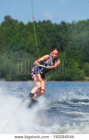 Slim Brunette Woman Riding Wakeboard On Lake