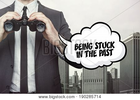 Being stuck in the past text on  blackboard with businessman and key