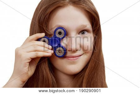 Cheerful girl, a schoolgirl holds a spinner, fidget hand toy in her hand, closes her eyes and smiles.