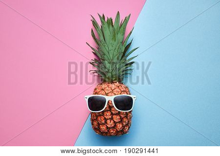 Fashion Hipster Pineapple Fruit. Bright Summer Color, Accessories. Tropical pineapple with Sunglasses. Creative Art concept. Minimal style. Pink blue summer party background