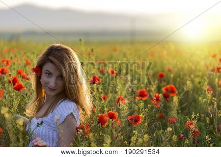 Woman in white dress among the full field of poppies