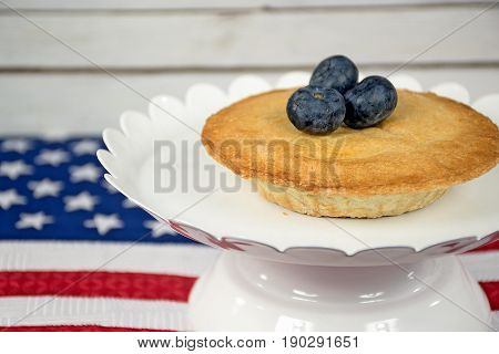 mini blueberry pie on white pedestal plate with American flag
