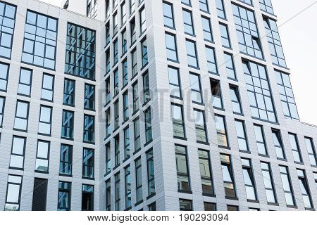 Modern architecture. Transparent walls with small ajar windows reflecting bright blue sky. Abstract glass background.