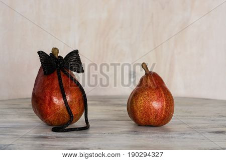 Two red pears on the wooden table. Conceptual photo with the pears. Rough in jewelry with a bow.