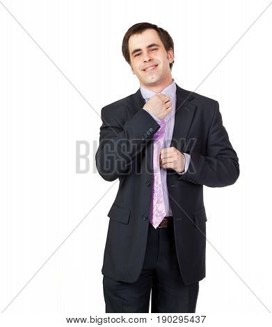 Portrait of young businessman corrects a tie on the shirt collar