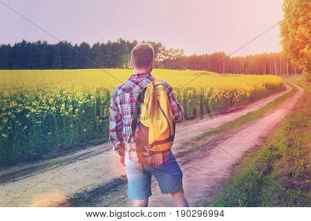 Young traveler alone on the road in the field look ahead at sunset. Lifestyle, walking pace, healthy way of life of a traveler's man