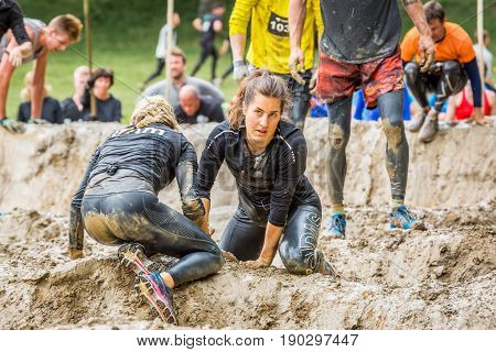 Stockholm Sweden - June 03 2017: Close up view two young caucasian woman struggling in a mud obstacle to complete the course of the annual event Toughest Stockholm. People in the background.