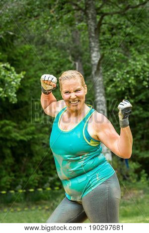 Stockholm Sweden - June 03 2017: Close up front view one caucasian chubby woman. Wet happy and smiling after completing a mud obstacle at the annual event Toughest Stockholm.