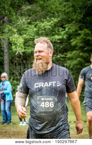 Stockholm Sweden - June 03 2017: Close up front view one caucasian man with full beard. Wet happy and smiling after completing a mud obstacle at the annual event Toughest Stockholm. A few people in the background.