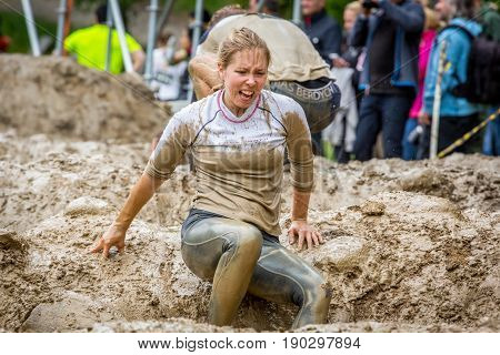 Stockholm Sweden - June 03 2017: Close up front view one caucasian woman struggling in an mud obstacle to complete the course of the annual event Toughest Stockholm. People in the background.