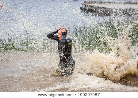 Stockholm Sweden - June 03 2017: Side view of a caucasian woman standing in muddy splashing water after riding a water slide during the annual event Toughest Stockholm.