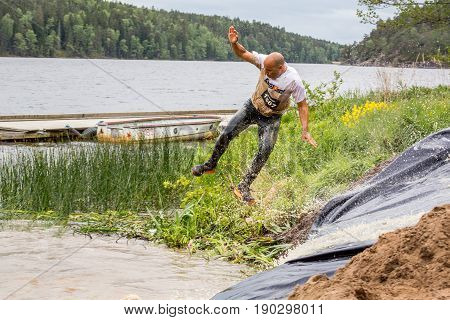 Stockholm Sweden - June 03 2017: Side view of a caucasian man in mid air after riding a water slide during the annual event Toughest Stockholm.