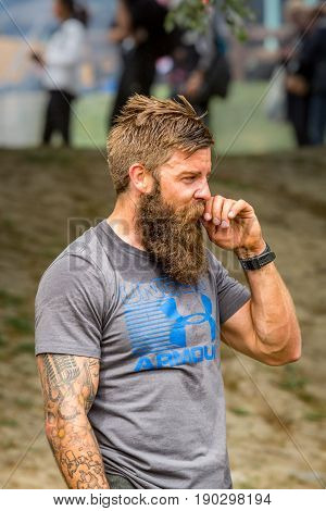 Stockholm Sweden - June 03 2017: Profile view of athletic sweaty young man with full beard resting after reaching the finish line in the event Toughest Stockholm. Blurred people in the background.