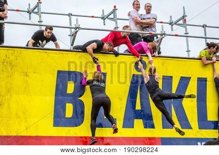 Stockholm Sweden - June 03 2017: Front view with group of young people hanging climbing and standing on an obstacle wall trying to complete the annual obstacle course event Toughest Stockholm.