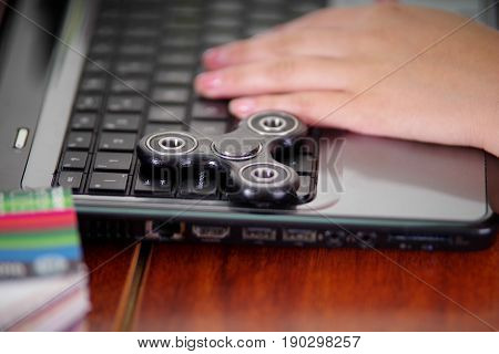 Young woman working in the computer and a popular fidget spinner toy over the laptop, on office background.