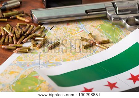 Close up of a shotgun and a revolver, cartridge belt with bullets with a blurred Iraq flag on a map, on wooden table.