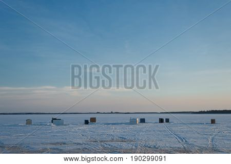 Ice fishing shacks out on the frozen harbour in rural Prince Edward Island, Canada.