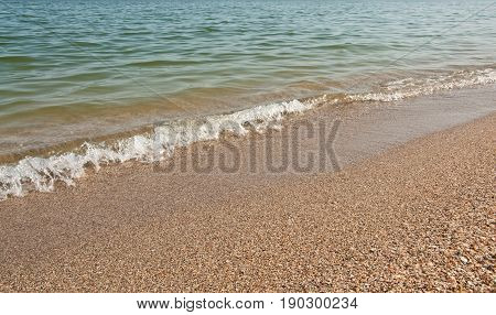 Beautiful seascape. Shells beach and clear blue water. Black Sea Ukraine