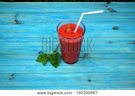 glass of strawberries, peach smoothie with straw on wooden table. Protein cocktail. Healthy drink. Fresh homemade smoothie. Healthy breakfast of smoothie,