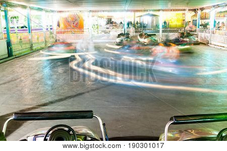 Two sit unused while other bumper cars whirl around the track
