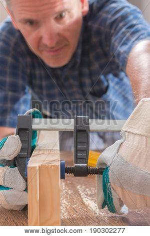 Man carpenter using bar clamp in a warkshop