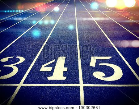 A glorious view of a track starting line with colorful bokeh lights.