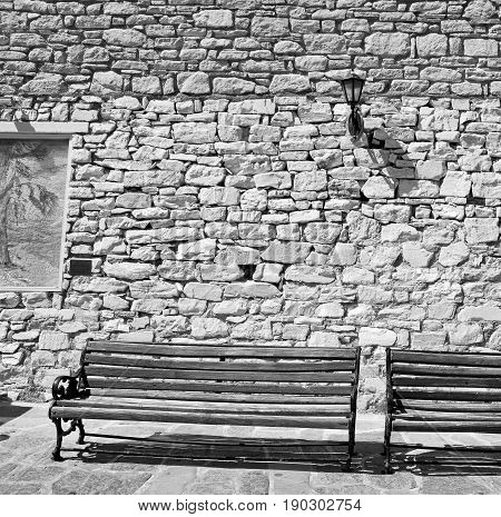In The Greece Island Of Paros Old Bench Near A Brick Antique Wall And Stone Pavement