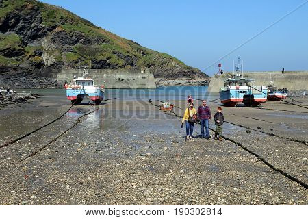 Port Isaac, Cornwall, Uk - April 8Th 2017: A Family Walks On The Sand At Low Tide Among Boats And Ot