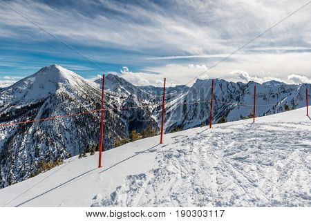 Ski tracks leading to the edge of an alpine plateau with a line of red demarcation poles overlooking a vista of snow-capped mountain peaks and valleys
