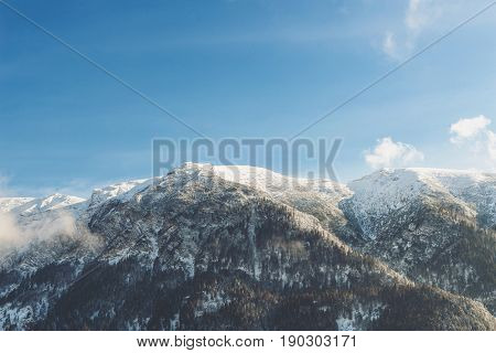 Snow covered mountains peaks with evergreen forests and wispy white clouds in a sunny blue sky in a scenic alpine landscape
