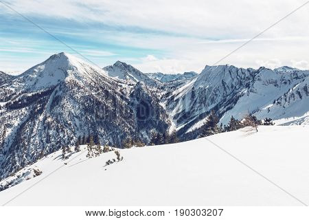 Pristine fresh white winter snow in the alps overlooking high snow-capped alpine peaks and forested valleys in a scenic landscape