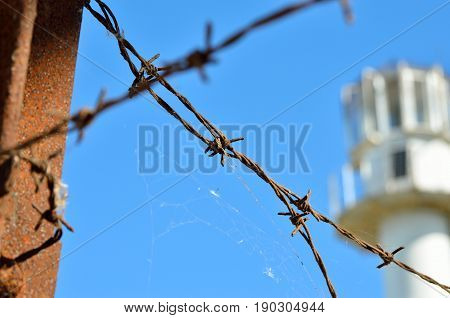 Barbed wire against the backdrop of the prison watchtower.