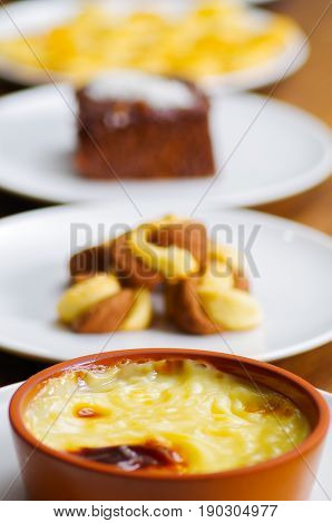 Turkish traditional dairy style rice pudding sutlac served in a crock on wood background.