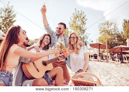 Group of happy young people having a picnic on the beach.Summer holidays vacation music and people concept.