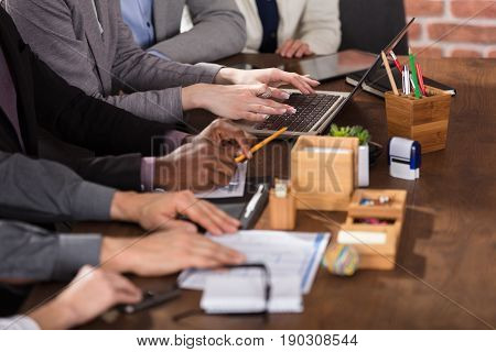 Close-up Of Businesspeople's Hand On Working Desk In Meeting Room