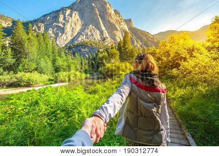 Hand in hand. Zumwalt Meadows hiking in Kings Canyon National Park, a large clearing in the forest with wildflowers and granite cliffs of Grand Sentinel. Female walking on a californian excursion hike