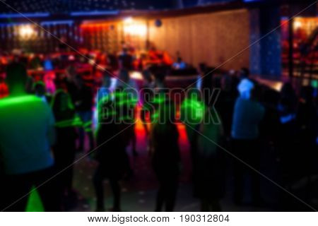 Blurred abstract image of people dancing in a nightclub. Men and women dancing in a nightclub on a dark background