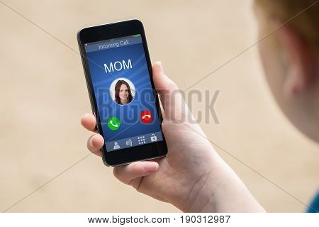 Close-up Of A Hand Holding Smart Phone With Mom's Incoming Call On Display