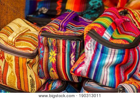 OTAVALO, ECUADOR - MAY 17, 2017: Beautiful andean traditional lunch box textile yarn and woven by hand in wool, colorful fabrics background.