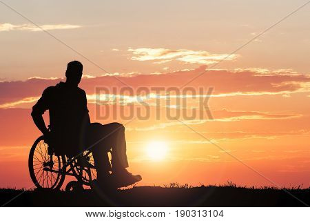 Silhouette Of A Person Sitting On Wheelchair Against Dramatic Sky At Sunset