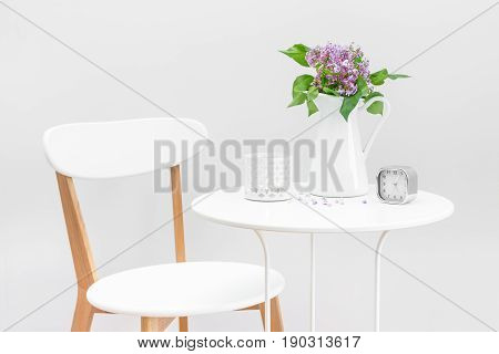 Elegant interior with white table and chair decorated with a bouquet of purple lilacs candle and clock.