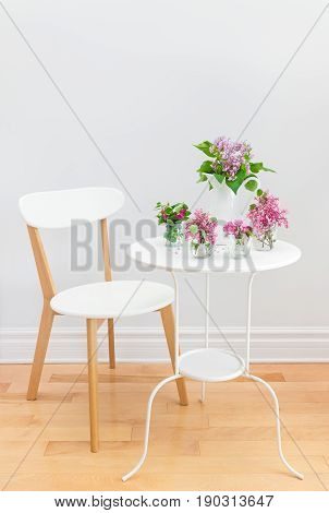 Elegant interior with white table and chair decorated with bouquets of spring flowers.