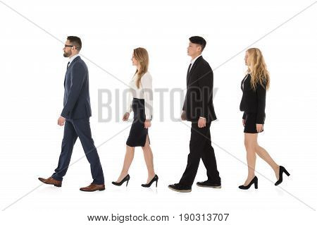 Multiracial Businesspeople Walking In Row Against White Background