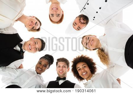 Low Angle View Of Happy Restaurant Staff Forming Huddle