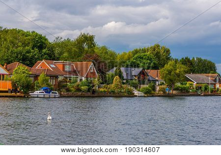 View Of The Other Side Of The River, Residential Houses Located On The Shore, Beautiful Boats, Lush
