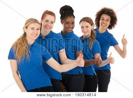 Group Of Young Female Janitors Standing In Row Gesturing Thumbs Up