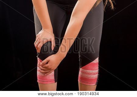 Close up of a beautiful young attractive sport woman holding injured knee suffering pain, in black background.