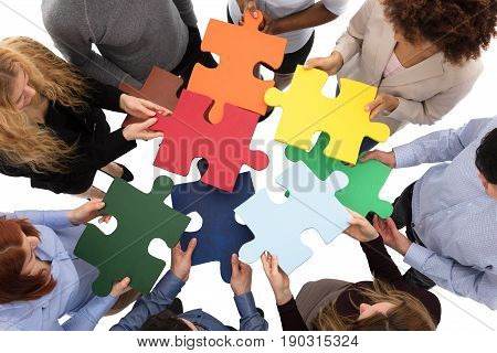 High Angle View Of College Students Solving Puzzle On White Background