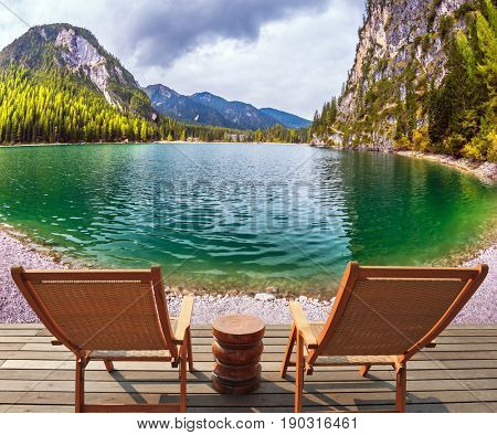 Two comfortable wooden deck chairs on the shore of the lake. Water reflects the surrounding mountains and forest. The concept of walking and eco-tourism